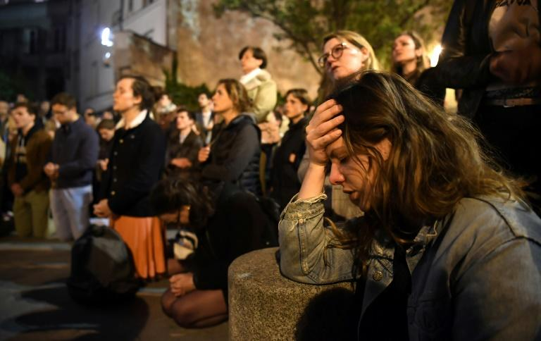 Crowds looked on in dismay and prayed as night fell and Notre-Dame continued to burn