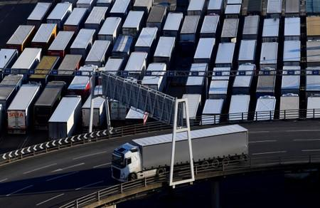 A lorry is driven past dozens of others parked after traveling by ferry between Britain and France at the Port of Dover