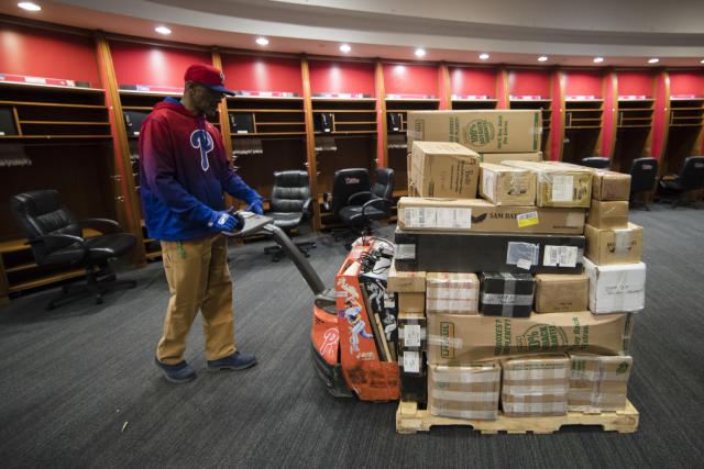 A worker hauls a load of Philadelphia Phillies' baseball equipment and personal belongings from the clubhouse, destined for spring training in Clearwater, Fla., Friday, Feb. 8, 2019, in Philadelphia. (AP Photo/Matt Rourke)