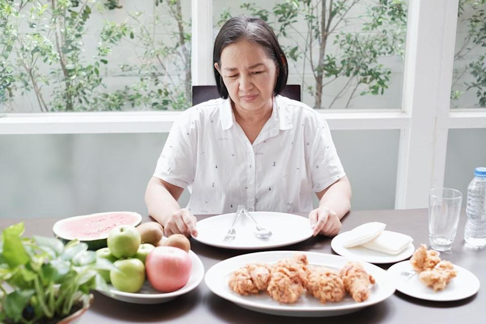older woman sitting at table with plates of food but not eating