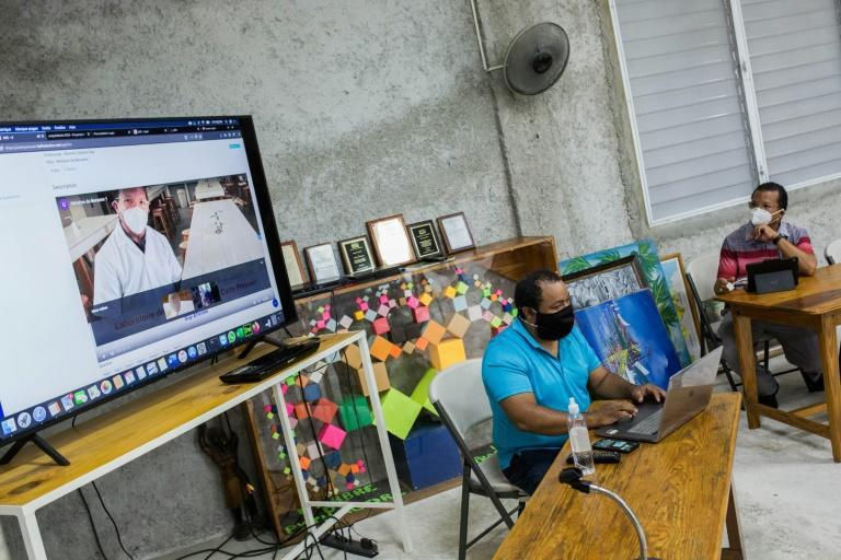 Guy Etienne (R), principal of the Catts Pressoir middle school in Port-au-Prince, demonstrates the Haiti school's internet platform, along with his son, Guy Philippe Etienne, who teaches robotics at the tech-focused school