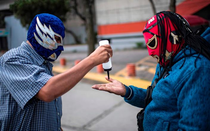 A Mexican fighter gives alcohol gel to a fellow man as they wait to receive supplies - AFP