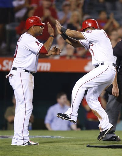 Los Angeles Angels' Vernon Wells, left, and Alberto Callaspo celebrate after they scored on a single by Chris Iannetta in the fourth inning of a baseball game against the Texas Rangers in Anaheim, Calif., Tuesday, Sept. 18, 2012. (AP Photo/Jae C. Hong)