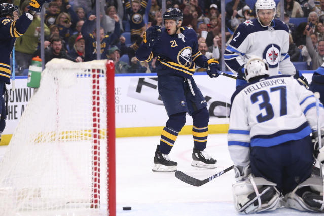 Buffalo Sabres forward Kyle Okposo (21) puts the puck past Winnipeg Jets goalie Connor Hellebuyck (37) during the first period of an NHL hockey game Sunday, Feb. 23, 2020, in Buffalo, N.Y. (AP Photo/Jeffrey T. Barnes)