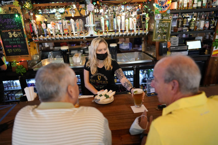 Bartender Angie Gibson, center, waits on customers at Mo's Irish Pub Wednesday, March 10, 2021, in Houston. Texas Gov. Greg Abbott allowed the state mandates for COVID-19 safety measures to expire Wednesday. (AP Photo/David J. Phillip)