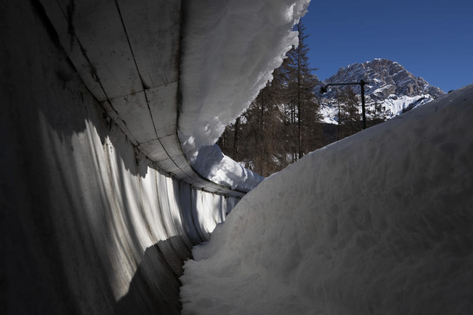 """FILE - The bobsled track in Cortina d'Ampezzo, Italy, is shown in this Wednesday, Feb. 17, 2021 file photo. The International Olympic Committee reluctantly accepted plans to spend 50 million euros ($60 million) to rebuild an abandoned bobsled track in Cortina d'Ampezzo for the 2026 Winter Games — as long as the funds stay out of the games' budget. After the IOC's periodic coordination commission visit Monday, April 19, 2021 which was held virtually, the Olympic body said it """"again expressed its concerns with regard to the legacy of the track."""" The century-old track in Cortina was closed 13 years ago for financial reasons. (AP Photo/Gabriele Facciotti, File)"""