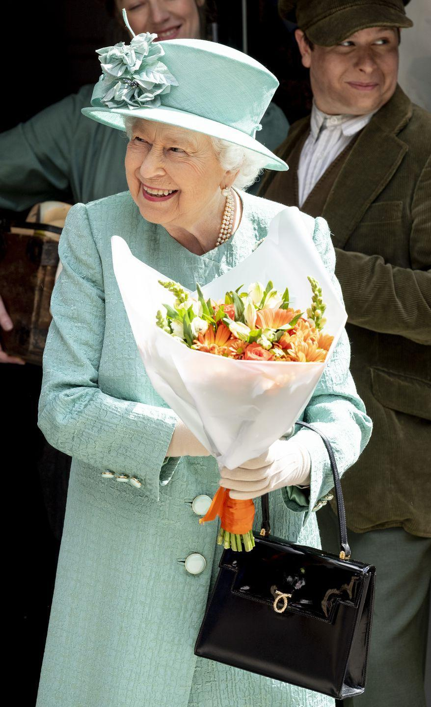 <p>Queen Elizabeth received a bouquet of flowers after visiting a replica of a Sainsbury's store in Covent Garden </p>
