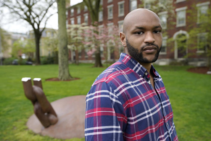 Brown University graduate Jason Carroll, a Maryland native whose ancestors were slaves in the Carolinas, stands for a portrait on the Brown campus in Providence, R.I., on Tuesday, May 4, 2021, near the Slavery Memorial, left, by sculptor Martin Puryear erected in 2014. Nearly two decades after launching its much-lauded reckoning with slavery, Brown hasn't taken any meaningful steps to compensate slave descendants themselves, argues Carroll. (AP Photo/Steven Senne)