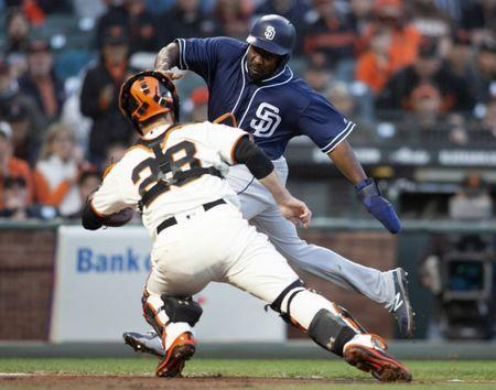 Jun 21, 2018; San Francisco, CA, USA; San Diego Padres baserunner Jose Pirela (right) tries to elude the tag of San Francisco Giants catcher Buster Posey (28) in the fifth inning at AT&T Park. Pirela tried to score from first base on a double by San Diego Padres outfielder Manuel Margot, but was tagged out. Mandatory Credit: D. Ross Cameron-USA TODAY Sports