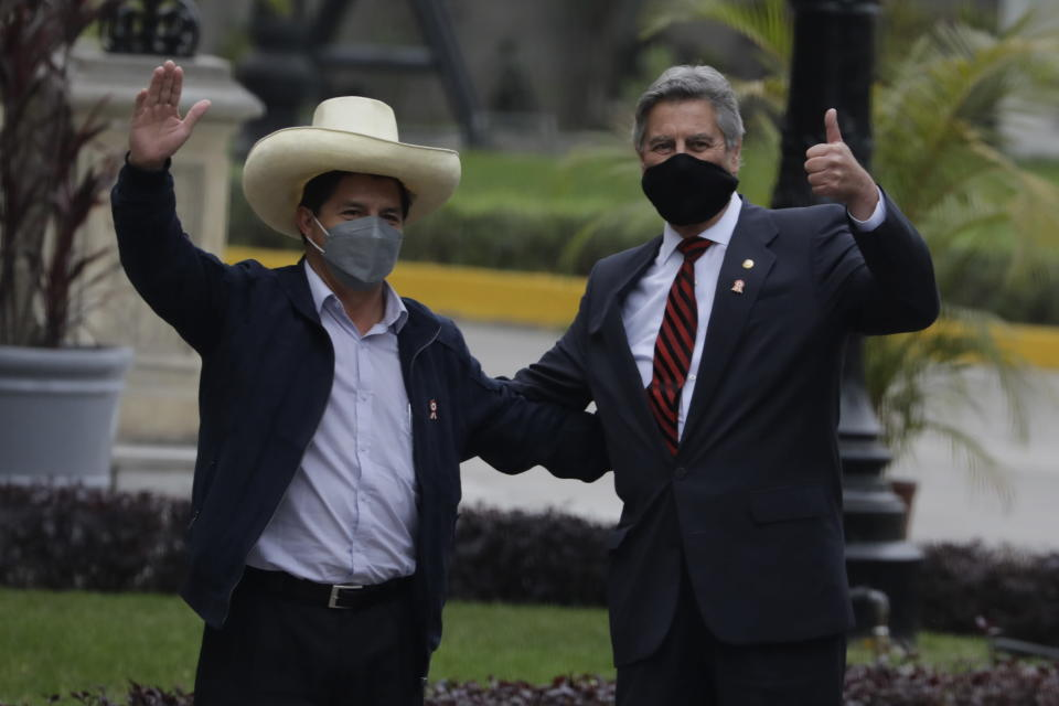 President-elect Pedro Castillo, left, poses for a photo with interim President Francisco Sagasti at the government palace after a transition meeting, in Lima, Peru, Wednesday, July 21, 2021. Castillo will be sworn in on July 28. (AP Photo/Gudalupe Pardo)