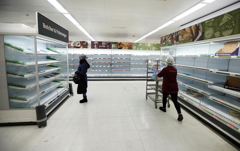 A Sainsbury's worker walks past a customer next to empty shelves at a Sainsbury's store in Harpenden as the spread of the coronavirus disease (COVID-19) continues, in Harpenden, Britain, March 18, 2020. REUTERS/Peter Cziborra
