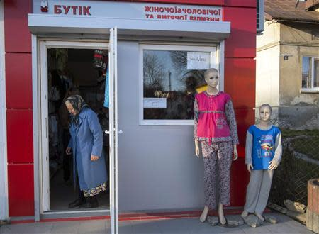 A woman leaves a shop in the small Ukrainian town of Pustomyty