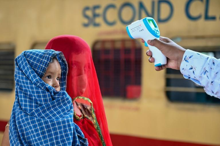 A health worker checks the body temperature of a passenger during a Covid-19 screening at a railway station in Mumbai