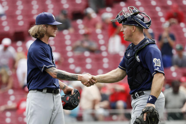 Milwaukee Brewers relief pitcher Josh Hader, left, celebrates with catcher Erik Kratz, right, after closing 11th inning of a baseball game against the Cincinnati Reds, Thursday, Aug. 30, 2018, in Cincinnati. (AP Photo/John Minchillo)