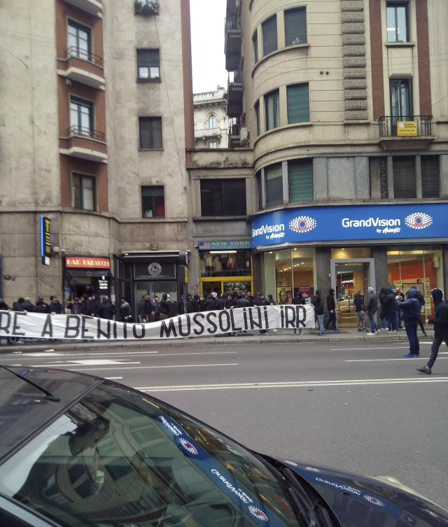 """In this photo taken on April 24, 2019 a banner with writing reading in Italian """"Honor to Benito Mussolini"""" is unfolded by Lazio soccer team fans in Milan. Fascist salutes, long a public taboo, have made their way out of the hooligan sections of soccer stadiums and into city streets, as demonstrated by a couple of dozen of the Roman football squad Lazio's historically right-wing and fascist ''ultra'' fans on visitors' turf in Milan. (Antonella LoConsolo via AP)"""