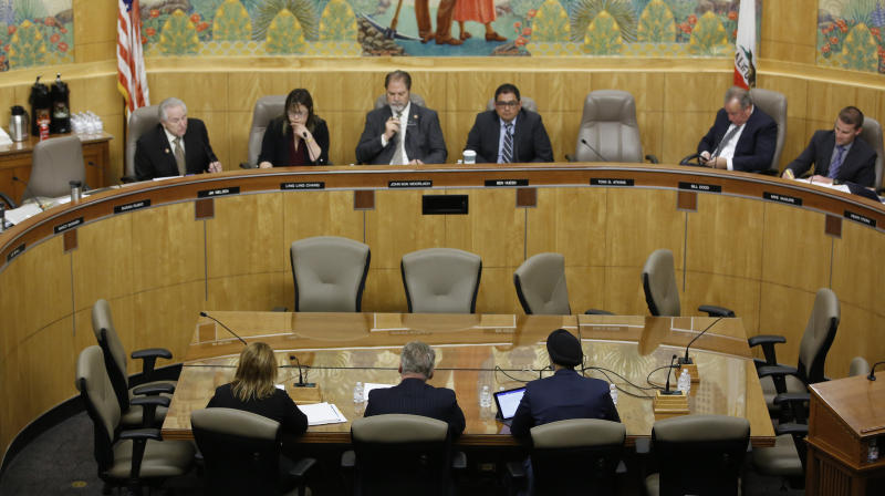 Pacific Gas & Electric CEO Bill Johnson, foreground center, discusses the utilities' decision to turn off power, last month, for millions of people to prevent California wildfires during an oversight hearing of the Energy, Utilities and Communications committee at the Capitol in Sacramento, Calif., Monday, Nov. 18, 2019. (AP Photo/Rich Pedroncelli)