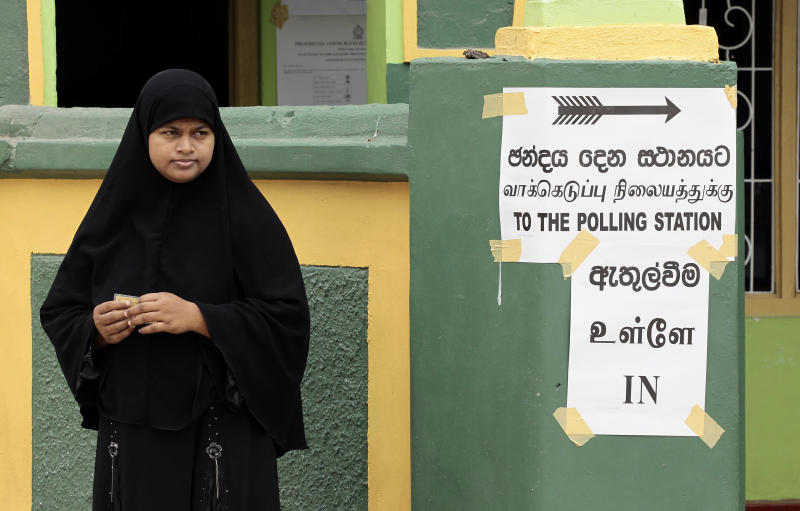 A Sri Lankan Muslim woman stands outside a polling a station after casting her vote at Kattankudi, Sri Lanka, Saturday, Sept. 8, 2012. Sri Lankans voted Saturday in a provincial assembly election seen as a test of whether ethnic minority Tamils still want self-rule or are satisfied with government-led economic development in a region devastated by a quarter-century civil war. As of noon, only small numbers of voters had turned out at polling booths in Batticaloa, one of three districts in Eastern Province. (AP Photo/Eranga Jayawardena)