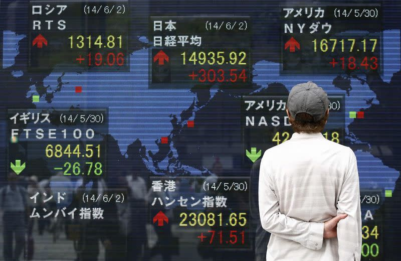 A pedestrian looks at an electronic board outside a brokerage in Tokyo