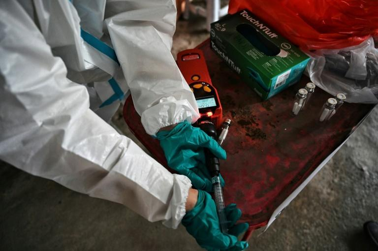 Researchers test sweat samples from vendors on the market (AFP/Lillian SUWANRUMPHA)