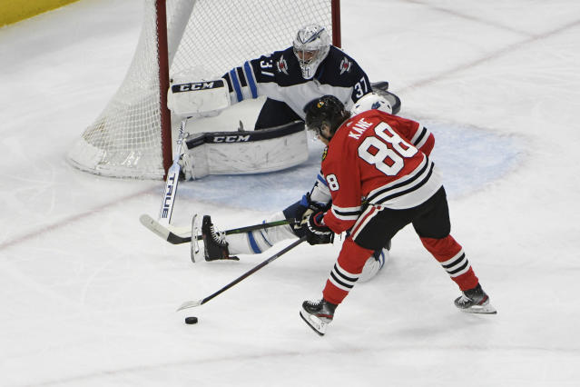 Chicago Blackhawks right wing Patrick Kane (88) skates in against Winnipeg Jets goaltender Connor Hellebuyck (37) during the first period of an NHL hockey game Sunday, Jan. 19, 2020, in Chicago. (AP Photo/David Banks)