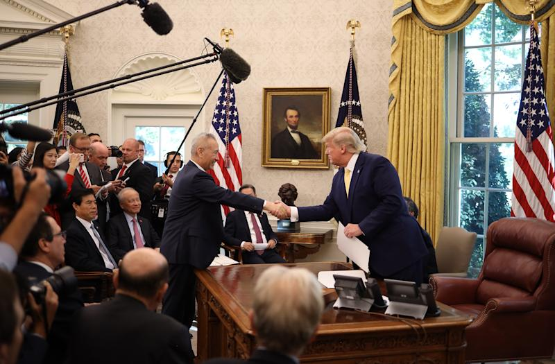 "WASHINGTON, DC - OCTOBER 11: U.S. President Donald Trump shakes hands with Chinese Vice Premier Liu He after announcing a ""phase one"" trade agreement with China in the Oval Office at the White House October 11, 2019 in Washington, DC. China and the United States have slapped each other with hundreds of billions of dollars in tariffs since the current trade war began between the world's two largest national economies in 2018. (Photo by Win McNamee/Getty Images)"