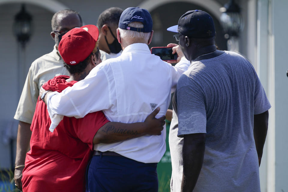 President Joe Biden takes a photo with residents as he tours a neighborhood impacted by Hurricane Ida, Friday, Sept. 3, 2021, in LaPlace, La. (AP Photo/Evan Vucci)