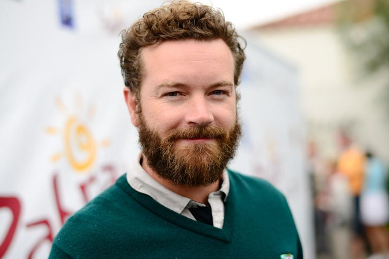 Danny Masterson headshot, smiling, wearing a green dress sweater and tie.