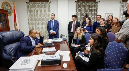 Sen. Bobby Powell, D-Riviera Beach, looks on his computer at gun control bills moving through the Senate as he talks with students from Marjory Stoneman Douglas High School and those that support their cause, following last week's mass shooting on their campus, in Tallahassee, Florida, February 20, 2018. REUTERS/Colin Hackley