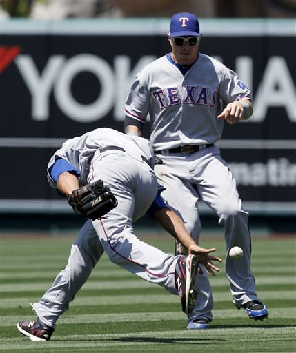 Texas Rangers right fielder Nelson Cruz can't get a hand on a fly ball hit by Los Angeles Angels' Mark Trumbo as center fielder Josh Hamilton looks on during the sixth inning of a baseball game in Anaheim, Calif., Sunday, June 3, 2012. (AP Photo/Chris Carlson)