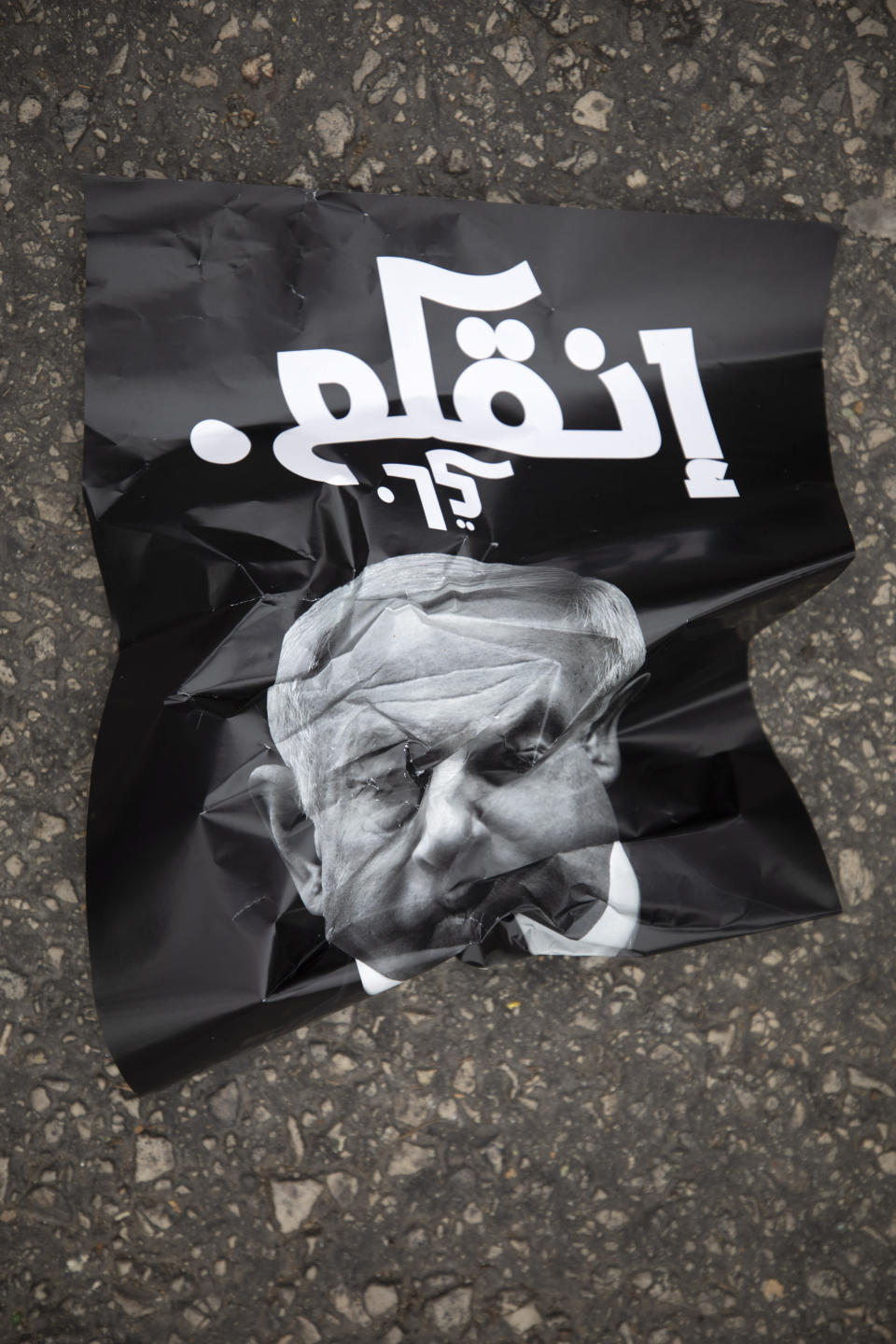 "A poster that reads, ""leave,"" lies on the ground during a demonstration against a visit by Israeli Prime Minister Benjamin Netanyahu to the northern Arab city of Nazareth, Israel, Wednesday, Jan. 13, 2021. Netanyahu, who has spent much of his long career casting Israel's Arab minority as a potential fifth column led by terrorist sympathizers, is now openly courting their support as he seeks reelection in the country's fourth vote in less than two years. (AP Photo/Sebastian Scheiner)"