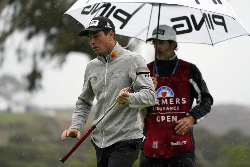 Viktor Hovland, left, of Norway, waits to putt on the eighth hole of the South Course during the second round of the Farmers Insurance Open golf tournament at Torrey Pines, Friday, Jan. 29, 2021, in San Diego. (AP Photo/Gregory Bull)