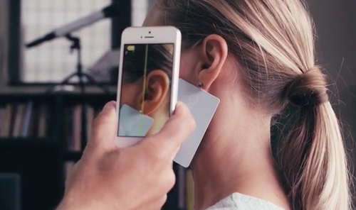 Smartphone taking a picture of a woman's ear