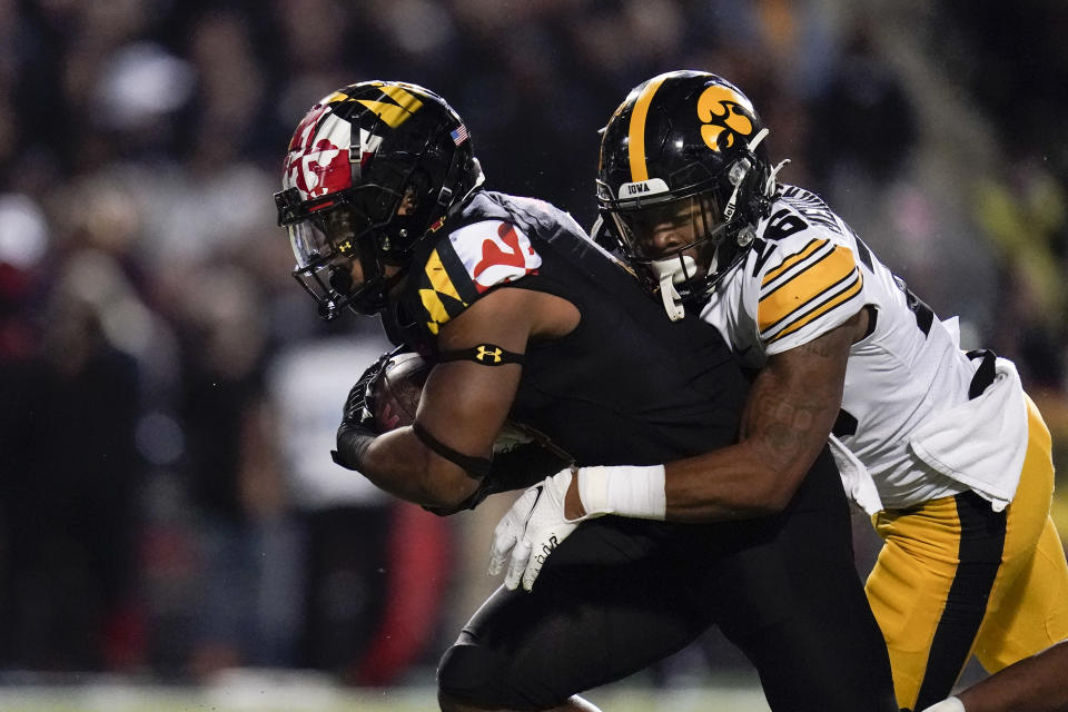 Maryland running back Isaiah Jacobs, left, rushes the ball as Iowa defensive back Kaevon Merriweather tries to bring him down during the second half of an NCAA college football game, Friday, Oct. 1, 2021, in College Park, Md. (AP Photo/Julio Cortez)