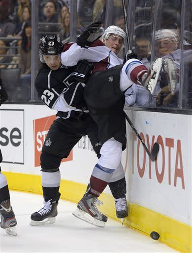 Los Angeles Kings right wing Dustin Brown, left, and Colorado Avalanche defenseman Tyson Barrie battle for the puck during the second period of their NHL hockey game, Thursday, April 11, 2013, in Los Angeles. (AP Photo/Mark J. Terrill)