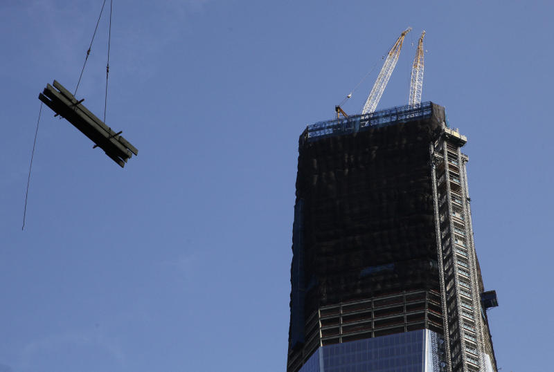 """FILE - In this Thursday, June 14, 2012 file photo, a load of steel is lifted to Four World Trade Center, not shown, past One World Trade Center, right, in New York. More than a decade after 9/11, no one's quite sure what to call the spot that was once a smoldering graveyard but is now the site of the fast-rising, 1,776-foot skyscraper that will replace the twin towers. Some are calling the new skyscraper """"One World Trade Center,"""" but it's still """"ground zero"""" to others. (AP Photo/Mark Lennihan, File)"""
