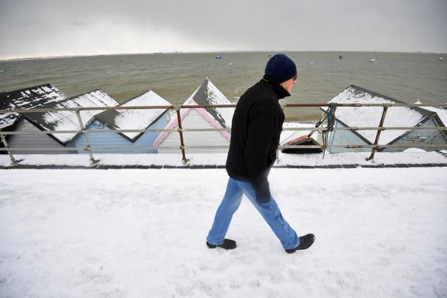 A man walks on the snow-covered seafront at Thorpe Bay, Essex