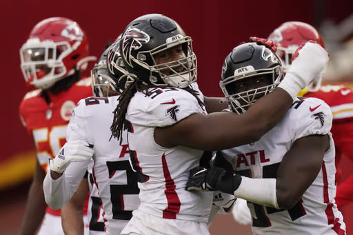 Atlanta Falcons linebacker Foyesade Oluokun, right, is congratulated by teammate Steven Means after intercepting a pass from Kansas City Chiefs quarterback Patrick Mahomes during the second half of an NFL football game, Sunday, Dec. 27, 2020, in Kansas City. (AP Photo/Jeff Roberson)