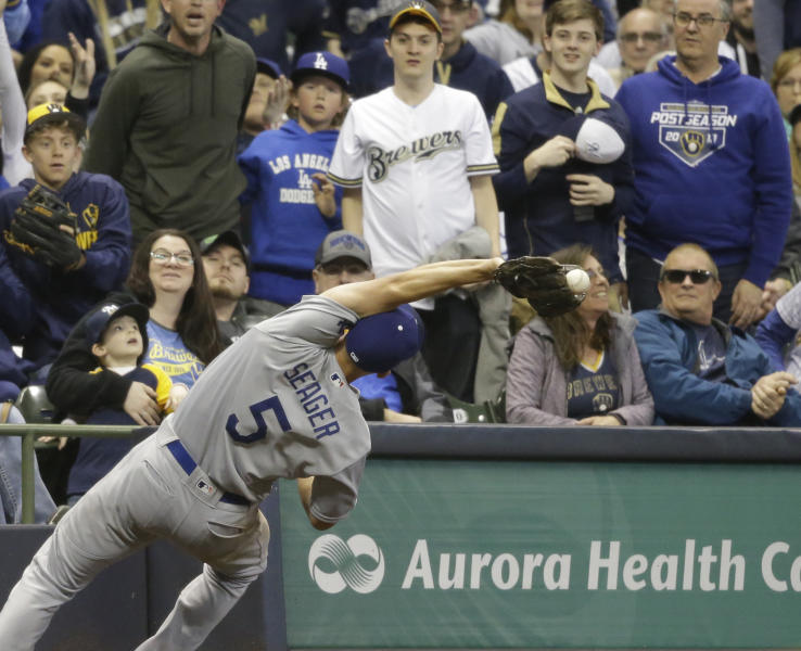 Los Angeles Dodgers' Corey Seager can't catch a foul ball hit by Milwaukee Brewers' Mike Moustakas during the seventh inning of a baseball game Friday, April 19, 2019, in Milwaukee. (AP Photo/Jeffrey Phelps)