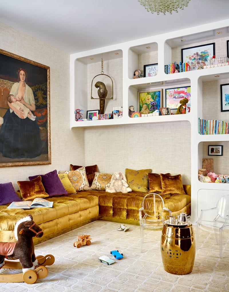 A custom built-in gold velvet sofa creates a bold focal point in the kids' den, which also includes handcrafted 1960s-style bookshelves and a table and chairs by Kartell. The vintage oil painting was a gift from actors Jeremy Renner and Kristoffer Winters, who found the work while shooting a movie in Argentina.