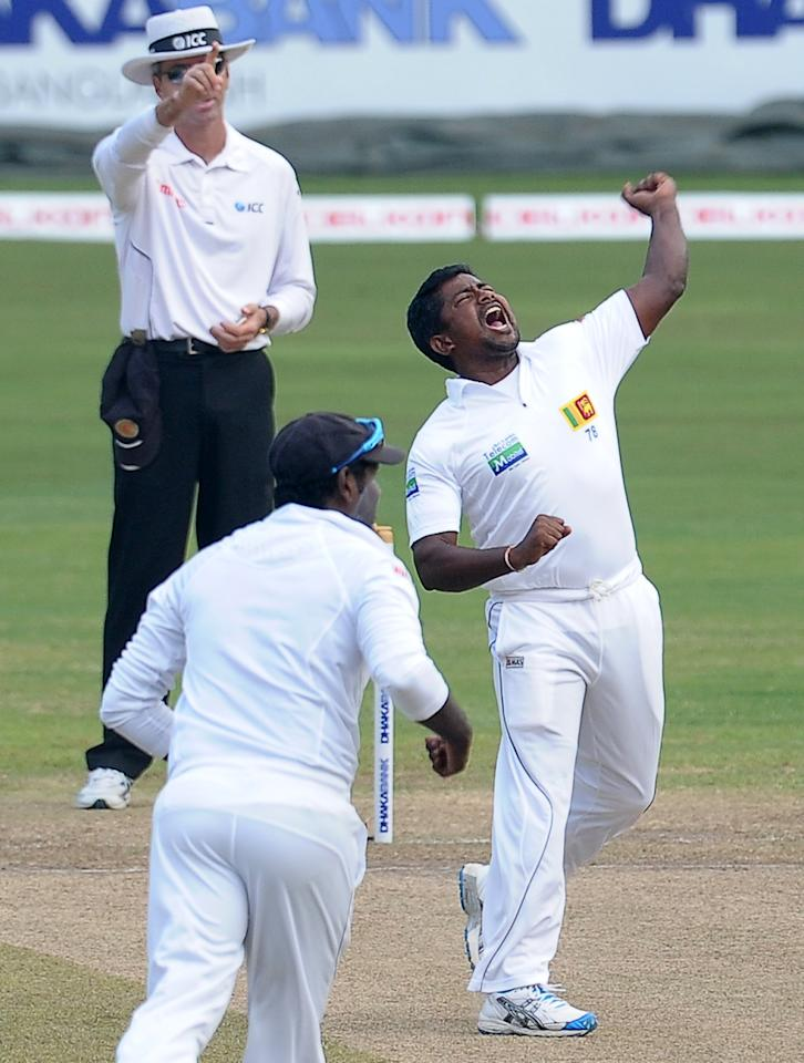 Sri Lankan cricketer Rangana Herath (R) celebrates after he dismissed Bangladeshi cricketer Mominul Haque during the fourth day of the second Test match between Sri Lanka and Bangladesh at the R. Premadasa Cricket Stadium in Colombo on March 19, 2013.   AFP PHOTO/ LAKRUWAN WANNIARACHCHI