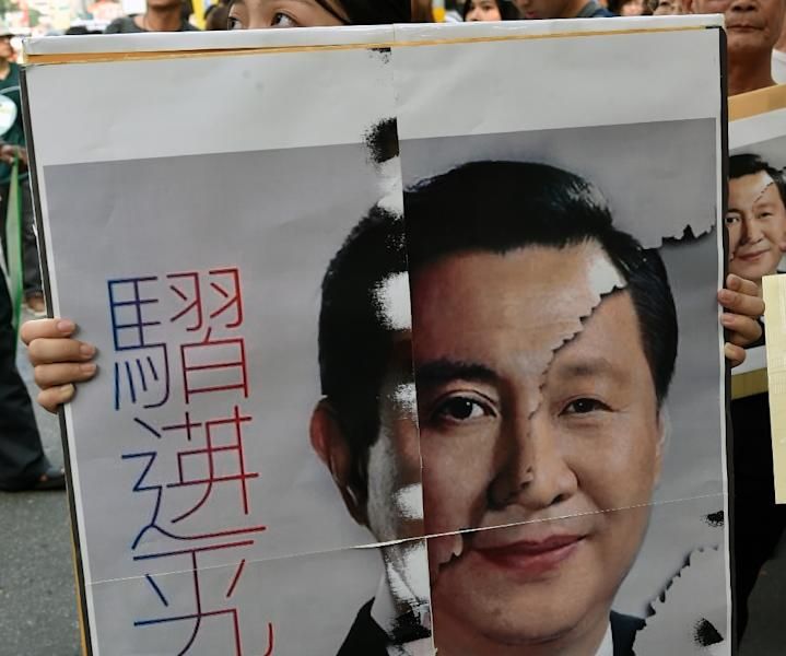 A Taiwanese protester displays combo picture of Presidents Ma and Xi during a demonstration in Taipei on November 7, 2015 (AFP Photo/Sam Yeh)