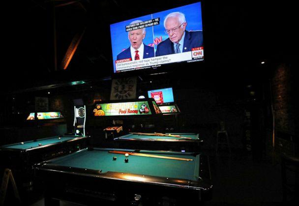 PHOTO: Democratic presidential candidates former Vice President Joe Biden and Sen. Bernie Sanders speak about the coronavirus crisis in a nearly empty restaurant/bar during the Democratic presidential debate, March 15, 2020 in Los Angeles. (Mario Tama/Getty Images)
