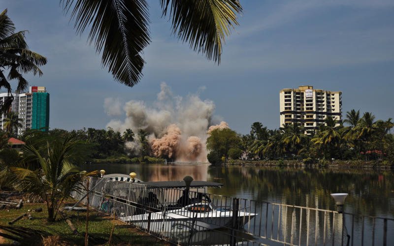 Alpha Serene, a water-front residential apartment, is razed to the ground by controlled implosion in Kochi, India, Saturday, Jan. 11. 2020. Authorities in southern Kerala state on Saturday razed down two high-rise luxury apartments using controlled implosion in one of the largest demolition drives in India involving residential complexes for violating environmental norms. (AP Photo/R S Iyer)