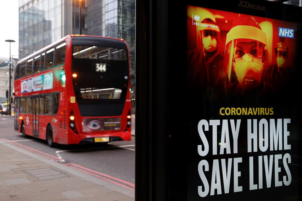 A bus drives past a government sign about the pandemic London. Photo: John Sibley/Reuters