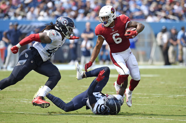 Arizona Cardinals running back James Conner (6) carries the ball against Tennessee Titans outside linebacker Bud Dupree (48) and cornerback Jackrabbit Jenkins (20) in the first half of an NFL football game Sunday, Sept. 12, 2021, in Nashville, Tenn. (AP Photo/Mark Zaleski)