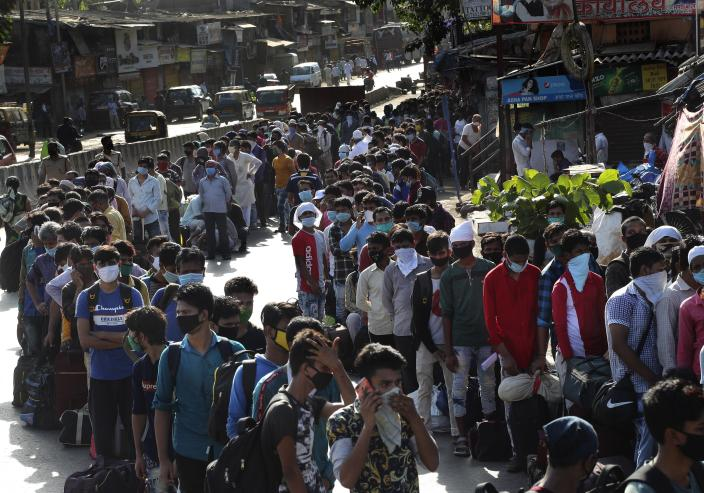 FILE - In this Friday, May 22, 2020 file photo migrant workers line up to board buses for their onward journey by train to their home states, at Dharavi, one of Asia's largest slums, in Mumbai, India. (AP Photo/Rafiq Maqbool)