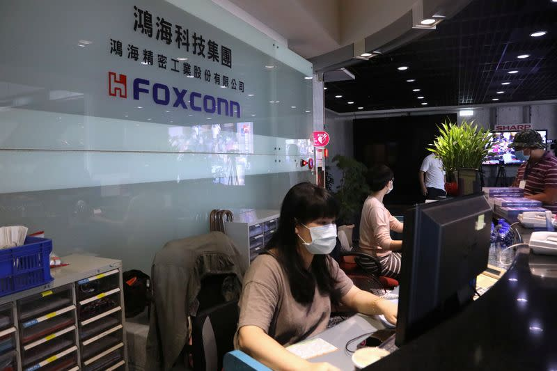 Staff wear masks to protect themselves from coronavirus disease (COVID-19), while listening to the annual general meeting at the lobby of Foxconn's office in Taipei,