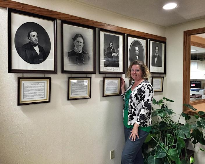Lee Ann Shearer, curator of the museum, stands next to framed photos.