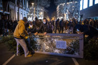 Demonstrators make barricades during clashes with police during a protest condemning the arrest of rap artist Pablo Hasél in Barcelona, Spain, Tuesday, Feb. 16, 2021. The imprisonment of a rap artist for his music praising terrorist violence and insulting the Spanish monarchy has set off a powder keg of pent-up rage this week in Spain. The arrest of Pablo Hasél has brought thousands to the streets for different reasons. The majority march under the banner of freedom of speech, but Hasél's lyrics also tap into a debate about the role of Spain's parliamentary monarchy after financial scandals involving the royal house. (AP Photo/Emilio Morenatti)