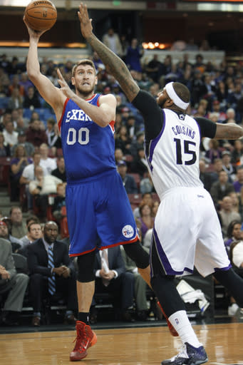 Philadelphia 76ers center Spencer Hawes (00) shoots over Sacramento Kings defender DeMarcus Cousins (15) during the first half of an NBA basketball game in Sacramento, Calif., on Thursday, Jan. 2, 2014.(AP Photo/Steve Yeater)